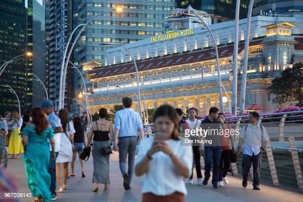 People walk on the Jubilee Bridge as the Fullerton Hotel stands in the background on June 4 2018 in Singapore US President Donald Trump announced on...