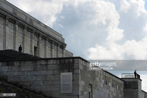 People walk on the main stage of the 'Zeppelinfeld' of the Reichsparteitagsgelaende in Nuremberg southern Germany on September 9 2013 It is the only...