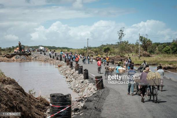 People walk on the N6 national road rebuilt in three days by China State Construction after the original road was destroyed by the Cyclone Idai in...
