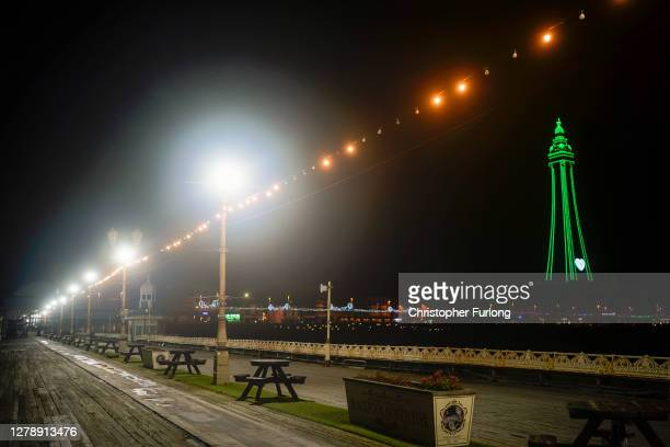People walk on the near deserted North Pier on October 06, 2020 in Blackpool, England. This year to help boost the tourism trade, which has been hit...