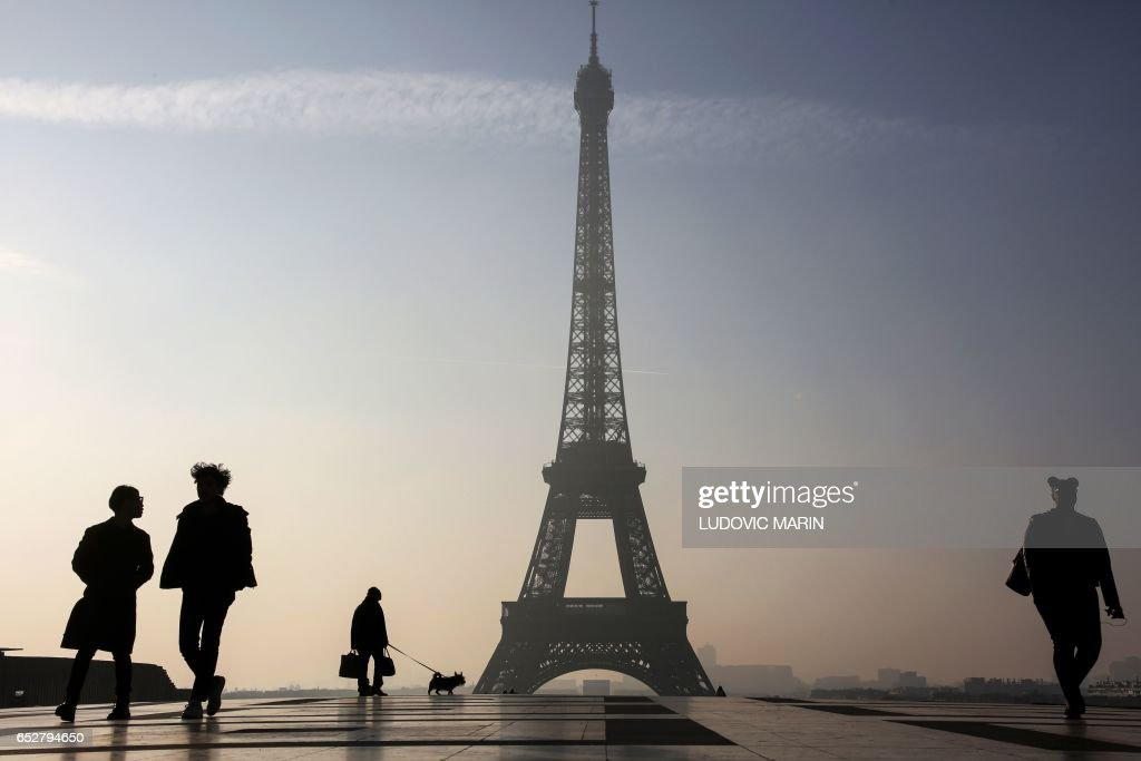 TOPSHOT - People walk on the Parvis des Droits de l'Homme square near the Eiffel tower in Paris on March 13, 2017. /