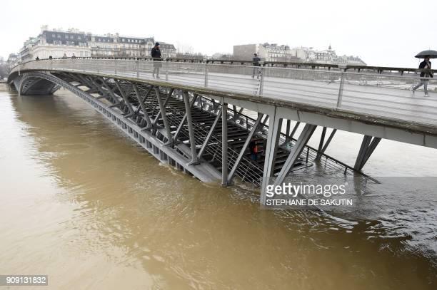 People walk on the Passerelle LeopoldSedarSenghor as the river Seine level has risen in Paris on January 23 2018 / AFP PHOTO / STEPHANE DE SAKUTIN