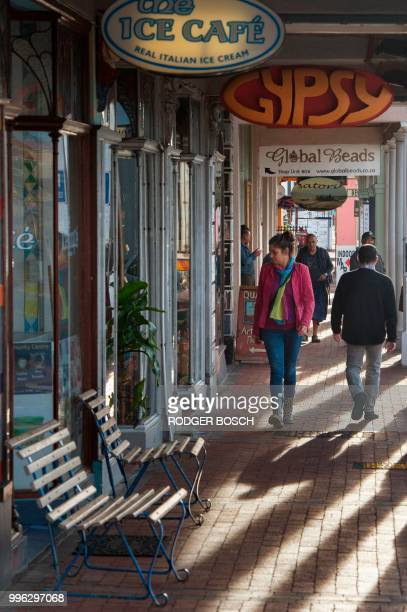 People walk on the pavement in Kalk Bay a trendy fishing village about 30km from the city centre on July 11 in Cape Town Kalk Bay with a combination...