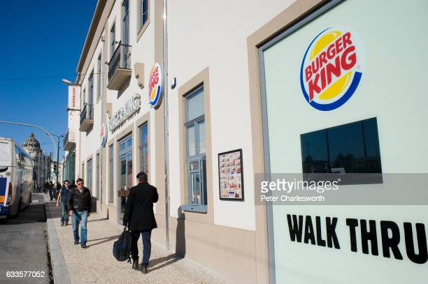 People walk on the pavement past a Burger King fast food restaurant featuring a 'walk thru'