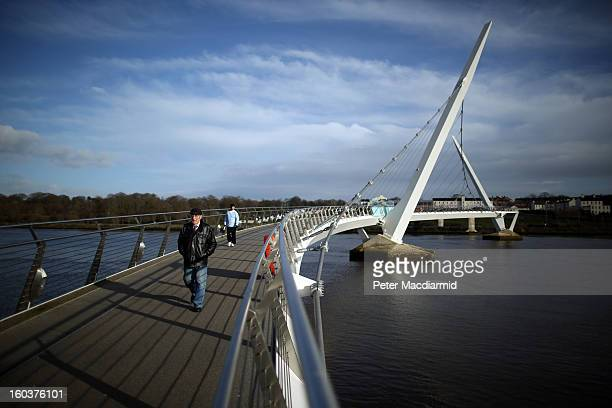 People walk on the Peace Bridge over the River Foyle on January 30, 2013 in Londonderry, Northern Ireland. A year of events have started as Derry...