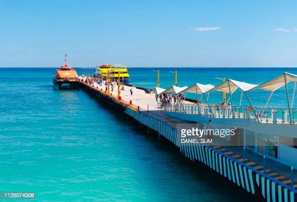 People walk on the pier of the ferries to the island of Cozumel in the seaside tourist resort of Playa del Carmen Quintana Roo State on February 15...