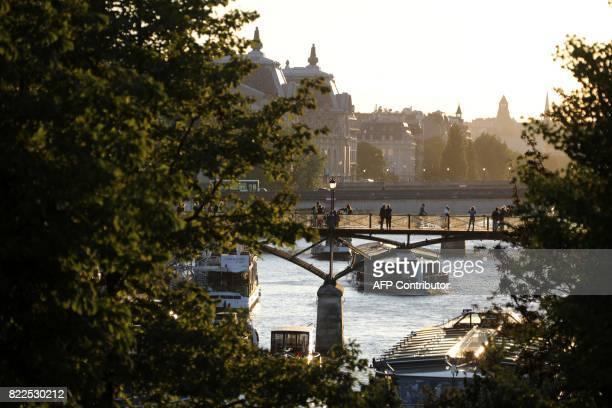 People walk on the Pont des Arts pedestrian bridge in Paris on July 25 2017 / AFP PHOTO / ludovic MARIN