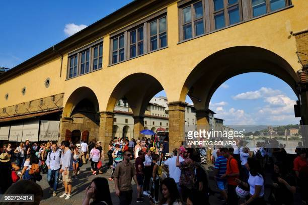 People walk on the Ponte Vecchio onto Arno river on May 26 2018 in central Florence