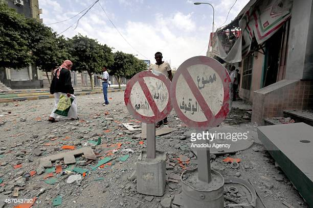People walk on the rubble of a road after the war crafts belonging to the Saudiled coalition carried out airstrikes on the Hada street in Sana'a...