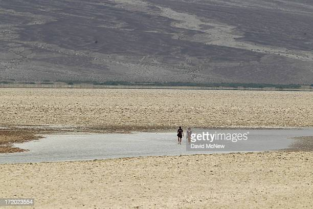 People walk on the salt flat at Badwater Basin the lowest point in the nation at 282 feet below sea level during a hot time of day as a heat wave...