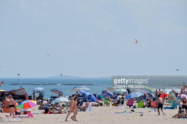 People walk on the sand at Hampton Beach in Hampton New Hampshire on August 5 as COVID19 cases in New England are on the rise Hampton Beach is close...