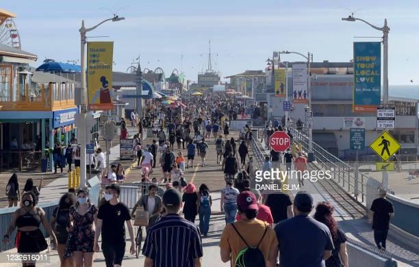 People walk on the Santa Monica Pier on April 30, 2021 in Santa Monica, California.
