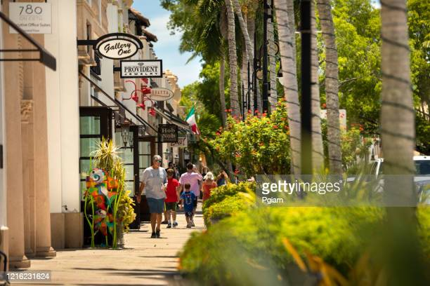 people walk on the sidewalk of main street downtown naples florida - naples florida stock pictures, royalty-free photos & images