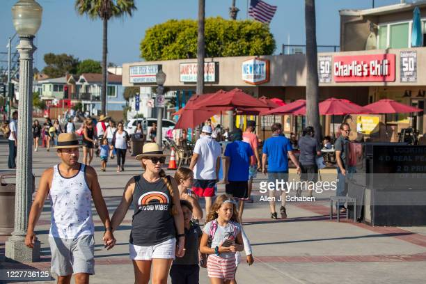 People walk on the sidewalk past businesses on a summer day Monday, July 20, 2020 in Newport Beach, CA.