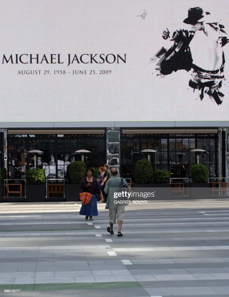 People walk on the sidewalk prior to a press conference in front of the Staples Center in Los Angeles, California on July 03, 2009, where a memorial service will be held on July 7 for Michael Jackson, who died June 25, 2009, at age 50.