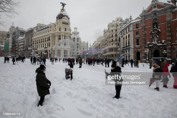 People walk on the snow along Calle Alcalá during heavy snowfall on January 09, 2021 in Madrid, Spain. Spain is on red alert for a second day due to...