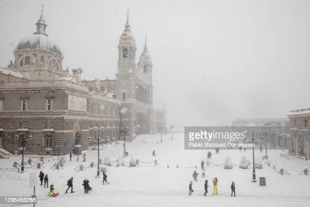 People walk on the snow next to La Almudena Cathedral during heavy snowfall on January 09, 2021 in Madrid, Spain. Spain is on red alert for a second...