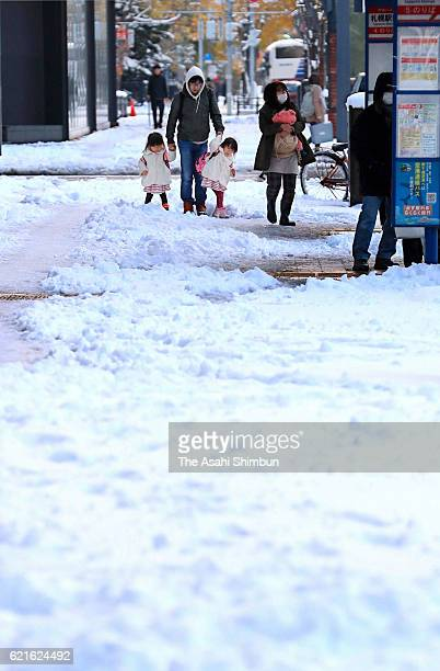People walk on the snowcovered street on November 6 2016 in Sapporo Hokkaido Japan A low pressure system passed over Hokkaido leading to the...