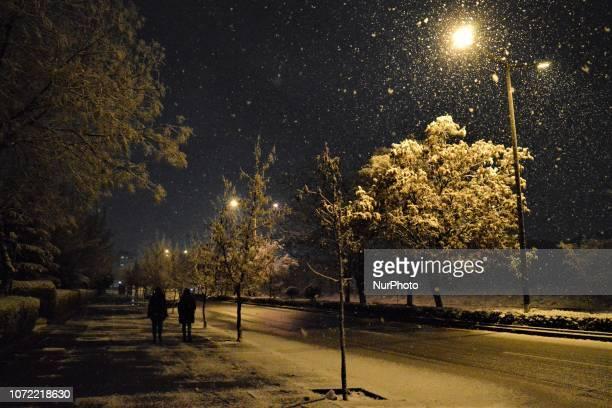 People walk on the street during a heavy snowfall in the winter season in Ankara Turkey on December 12 2018