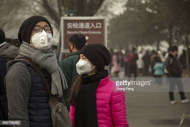 People walk on the street, wearing special mask to prevent breathing in the toxic air particles. On the first day of 2017, Beijing suffered its first...