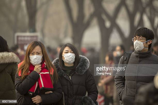 People walk on the street wearing special mask to prevent breathing in the toxic air particles On the first day of 2017 Beijing suffered its first...