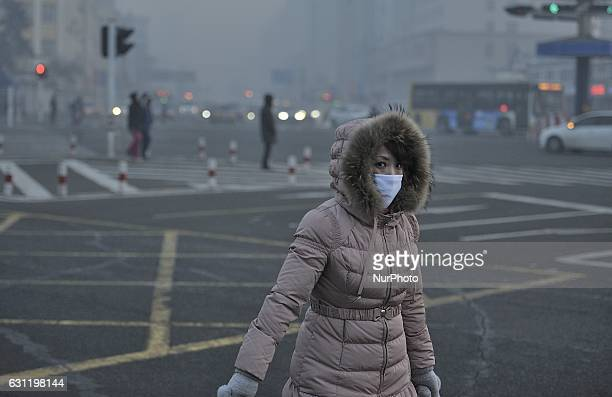 People walk on the street wearing special mask to prevent breathing in the toxic air particles in harbin city of china on Jan 8 2017Harbin suffered...
