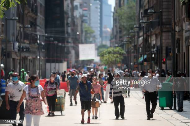 People walk on the streets of downtown on July 15, 2020 in Mexico City, Mexico. While most of the Mexican States remain in orange color level, some...