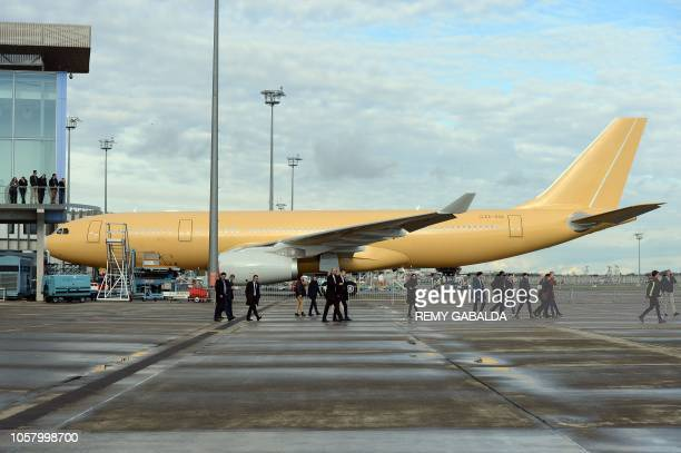 People walk on the tarmac during a visit of the Airbus A330800 aircraft before its first flight from Toulouse Blagnac airport near Colomiers on...