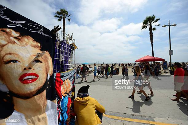 People walk on the Venice Beach boardwalk on August 4 2013 One day earlier 32yearold Italian newlywed Alice Gruppioni was killed after a man slammed...