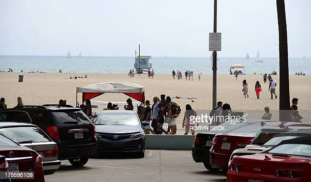 People walk on the Venice Beach boardwalk on August 4 2013 One day earlier Italian newlywed Alice Gruppioni was killed after a man slammed his car...