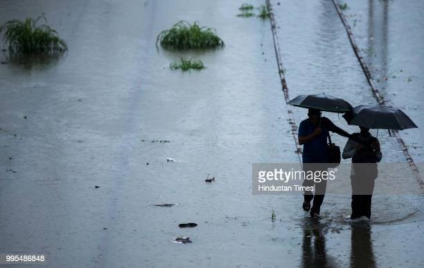 People walk on the waterlogged railway tracks at Matunga on July 9 2018 in Mumbai India Indias financial capital and its surrounding districts were...