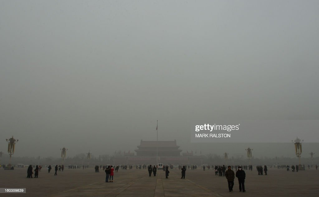 People walk on Tiananmen Square in front of Tiananmen Gate during heavy air pollution in Beijing on January 30, 2013