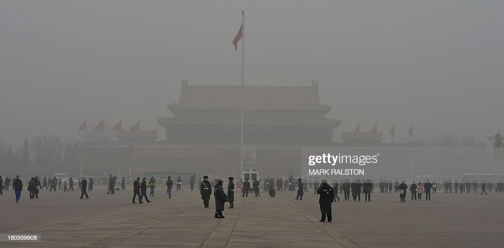 People walk on Tiananmen Square in front of Tiananmen Gate during heavy air pollution in Beijing on January 30, 2013. Beijing urged residents to stay indoors on January 30 as emergency measures were rolled out aimed at countering a heavy cloud of smog blanketing the Chinese capital and swathes of the country. AFP PHOTO/Mark RALSTON