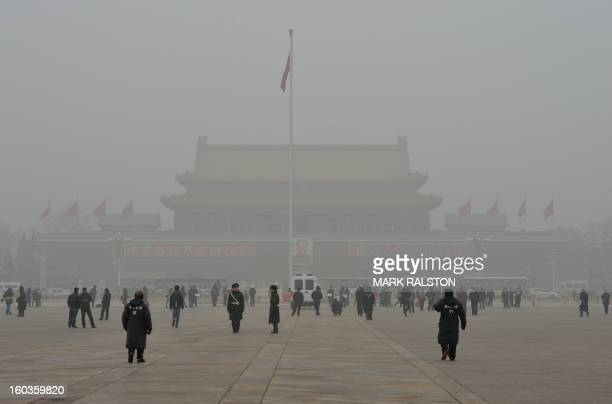 People walk on Tiananmen Square in front of Tiananmen Gate with the portrait of Mao Zedong during heavy air pollution in Beijing on January 30, 2013....