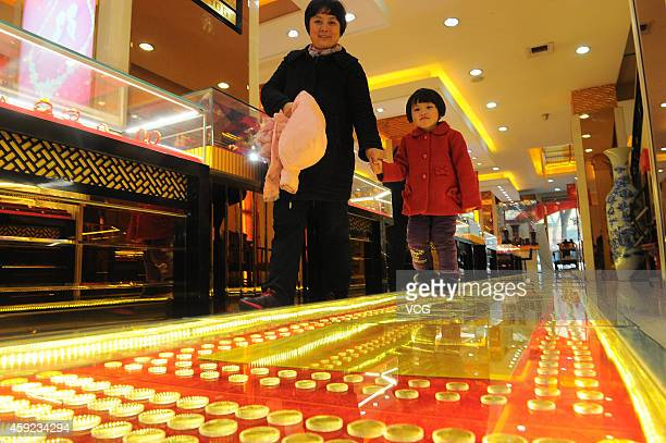 People walk on twelvemeterlong golden road on November 19 2014 in Taiyuan Shanxi province of China A jewelry shop paved a twelvemeterlong road with...