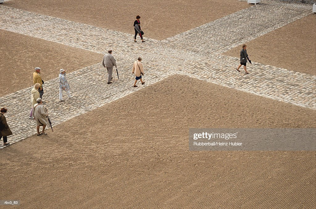people walk on white stones forming a cross on brown sand : Stockfoto