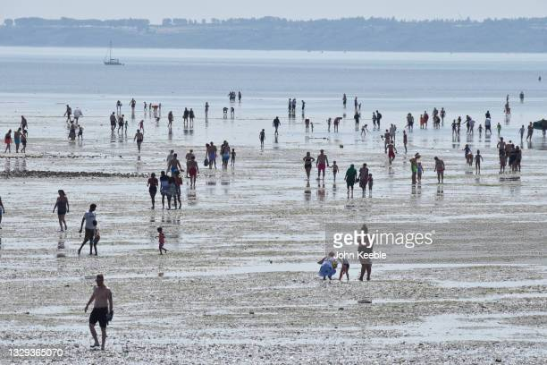 People walk out at low tide into the sea as they gather to enjoy the warm sunny weather on Jubilee beach on July 18, 2021 in Southend-on-sea,...