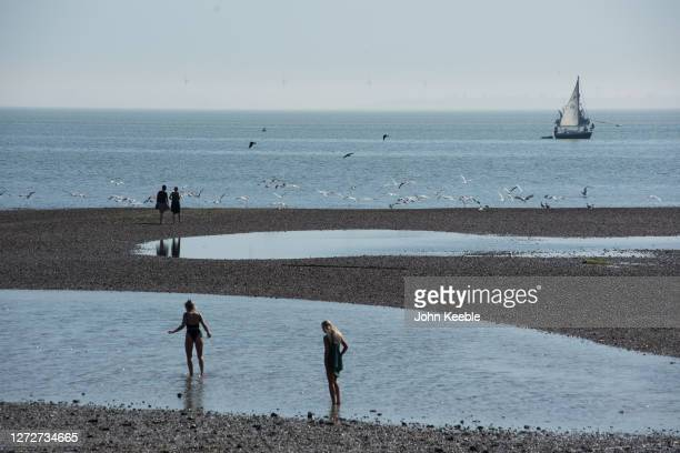 People walk out into the sea as seagulls take flight on September 14 2020 in Southend on Sea England Parts of the UK are expected to hit 29 degrees...
