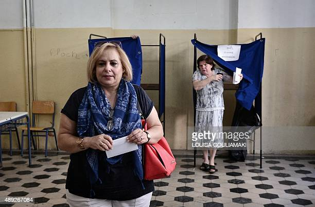 People walk out of polling booths prior to cast their vote at a polling station in central Athens on September 20 2015 Over 98 million Greeks were...