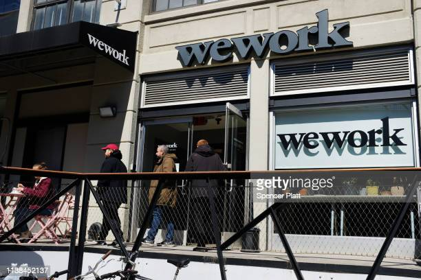 People walk out of the co-working space WeWork in the Williamsburg neighborhood in Brooklyn on March 26, 2019 in New York City. WeWork, which lets...