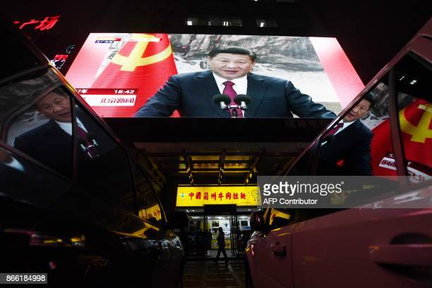 People walk outside a shop below a screen showing news coverage about Chinese President Xi Jinping, in Beijing on October 25, 2017. Chinese President...