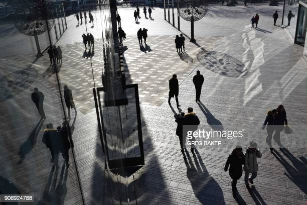 TOPSHOT People walk outside a shopping mall in Beijing on January 19 2018 China's economy grew a forecastbeating 69 percent in 2017 picking up steam...