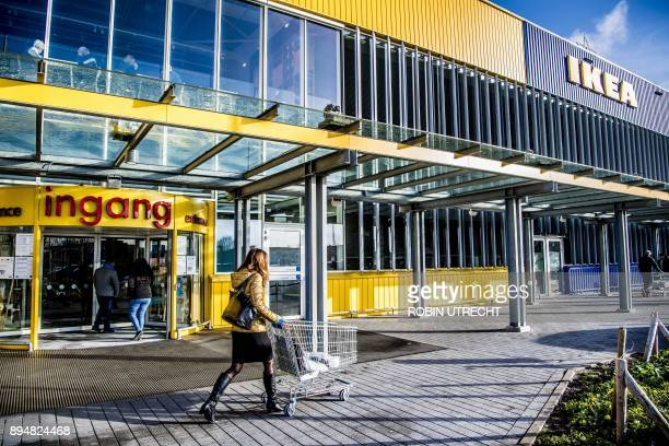 People walk outside a store of Swedish furniture giant Ikea in Delft the Netherlands on December 18 2017 The EU on December 18 opened an indepth...