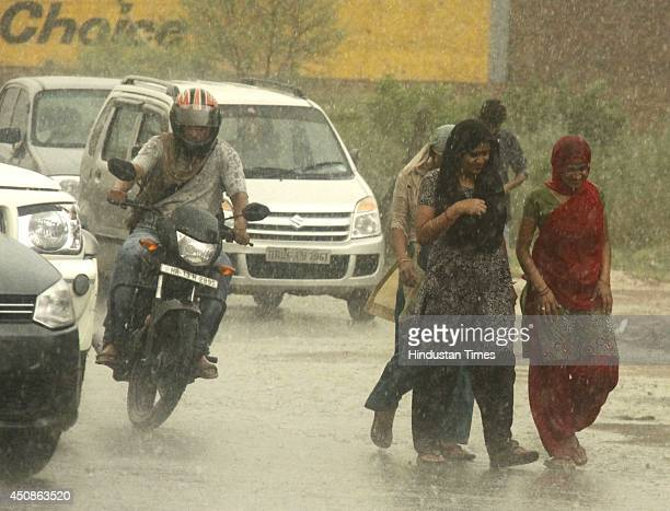 People walk outside as city witnesses heavy rain fall after a dust storm due to which temperature has fallen by few degrees on June 18 2014 in...