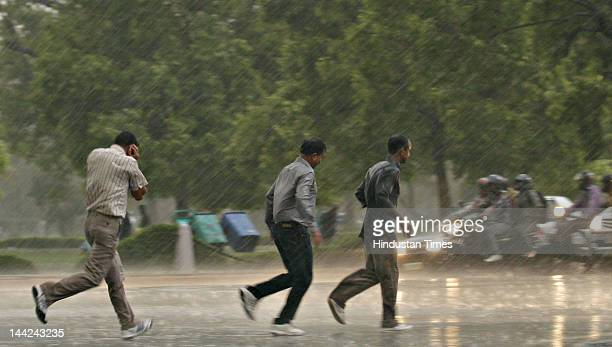 People walk outside as Delhi witnesses heavy rain fall after a dust storm due to which temperature has fallen by few degrees on May 12 2012 in New...
