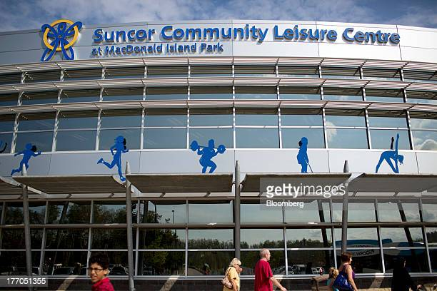 People walk outside he Suncor Community Leisure Centre at Macdonald Island Park in Fort McMurray Alberta Canada on Tuesday Aug 13 2013 Canadian oil...