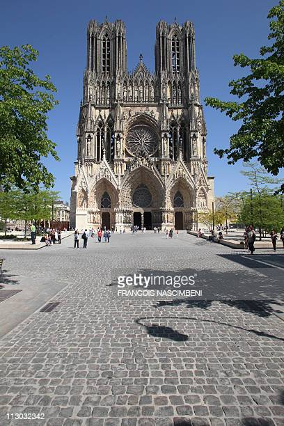 JULIEN People walk outside NotreDame Cathedral of Reims northeastern France on April 22 2011 The Gothic art masterpiece also known as the Coronation...