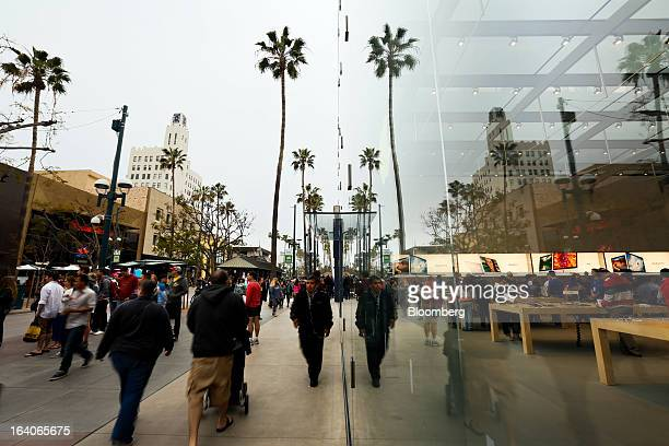 People walk outside of the Apple Inc Computer store on the Third Street Promenade in Santa Monica California US on on Saturday March 16 2013 Apple...