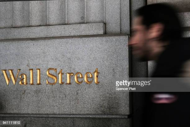 People walk outside of the New York Stock Exchange on April 2 2018 in New York City In afternoon trading the Dow dropped over 700 points on Monday as...