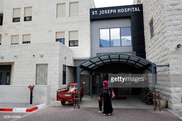 People walk outside of the Saint Joseph hospital in East Jerusalem on September 9 2018 The United States plans to cut $25 million in aid to six...